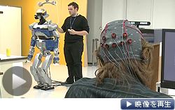 ヘッドギアを装着した研究員の脳波をセンサーが読み取って人型ロボットに伝達する